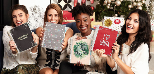 planner girls holding erin condren life planners with holiday and christmas covers