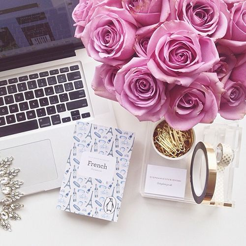 Trendy Office White Desk with Open Laptop, Gold Desk Accessories and Stationery, and Fresh Pink Roses Feminine Office and Home Decor