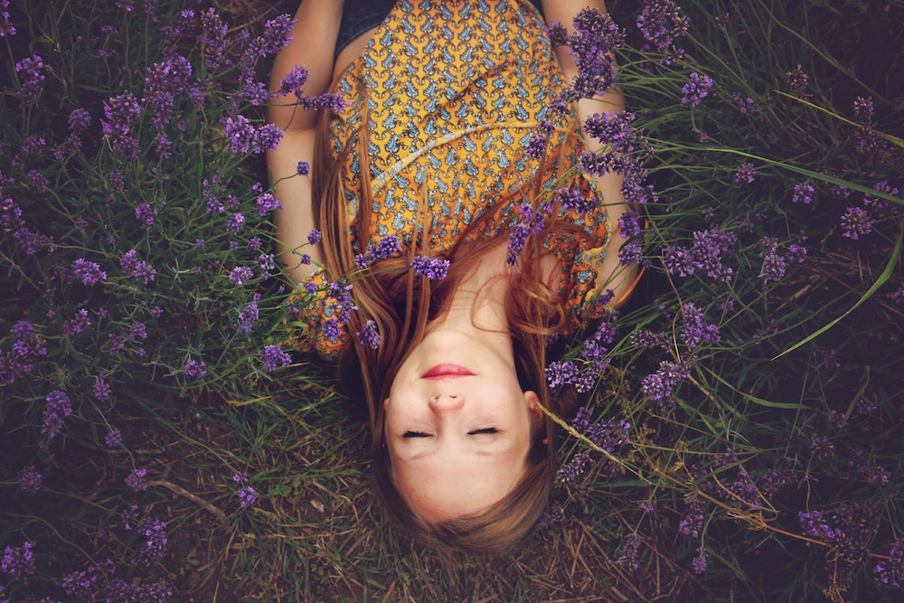 Learning to Choose Better Thoughts | Happy As Annie - We can't control our thoughts, but we can choose better thoughts to engage in and listen to. A mindfulness meditation practice can retrain our brains to choose better thoughts and reject unwanted or harmful ones. (Woman lying on ground on her back with eyes closed among purple flowers)