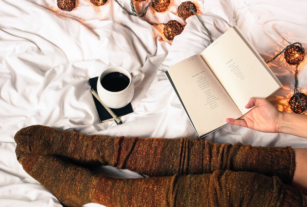 Why You Don't Need to Discover Your Passion | Happy As Annie's book club, Best Life Book Club, reads Big Magic by Elizabeth Gilbert (Close up of woman in knee-high brown socks laying in bed with coffee, string lights, and book of poetry open in her hand)