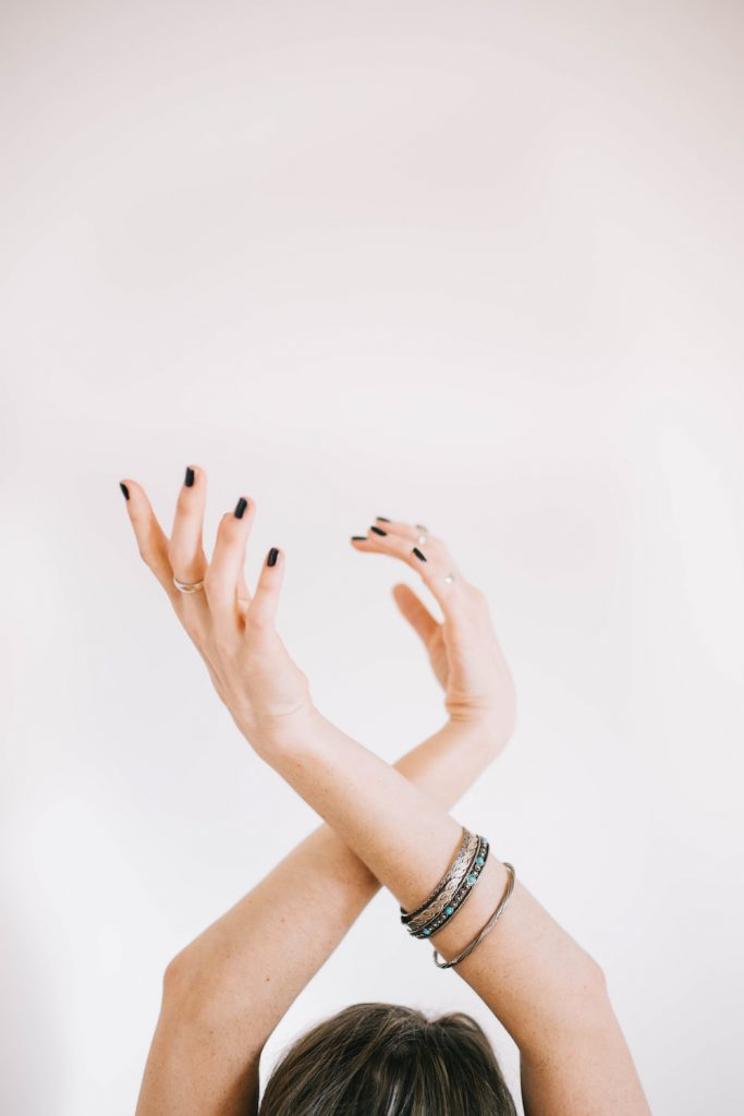 Happy As Annie | Having trouble sticking to a new routine or reaching a challenging goal? Do this first! How mental contrasting, rather than being blindly positive, can actually help us succeed. (Woman's nail polished hands crossed gracefully above her head)