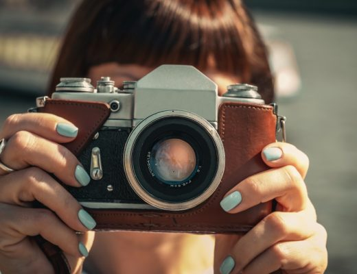 Girl holding vinrage camera in brown leather case in front of her face, mint green nail polish