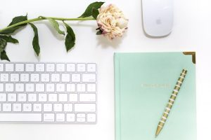 "Mint green ""Full of Ideas"" notebook, gold pen, flower, and keyboard and mousepad on white table"