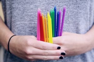 Girl in gray shirt and black nail polish holding several tall skinny rainbow colored candles in her hands