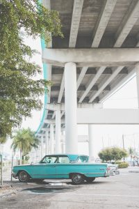 Turquoise vintage car parked in lot under bridge