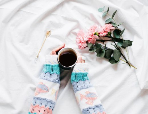 Girl in pastel colored knit sweater holding coffee mug against white sheets