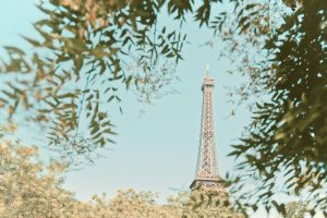 Eiffel Tower against blue sky with trees in foreground