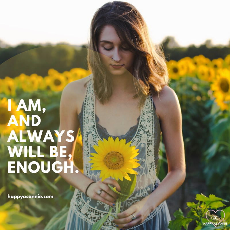 "Happy As Annie | 10 Positive Affirmations for Women that Empower and Uplift (Woman in dress standing in sunflower field holding sunflower in front of her with text overlay that says ""I am, and always will be, enough."""
