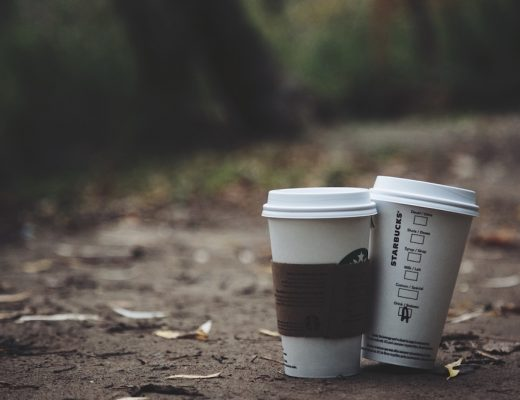 Two starbucks to-go cups sitting on ground in park