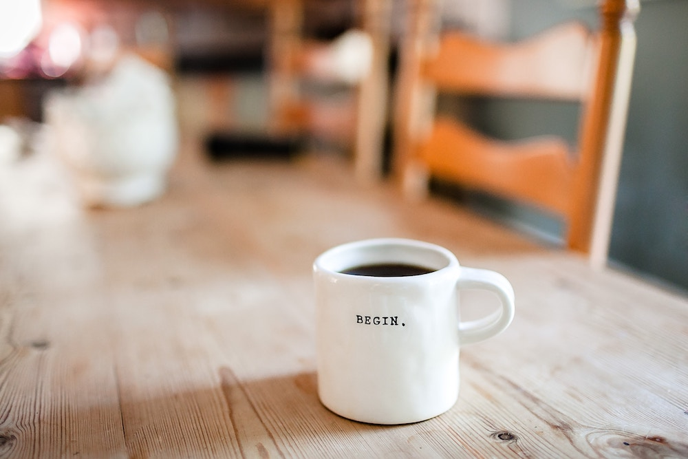 """Coffee in white mug that says """"begin"""" on a wooden table"""
