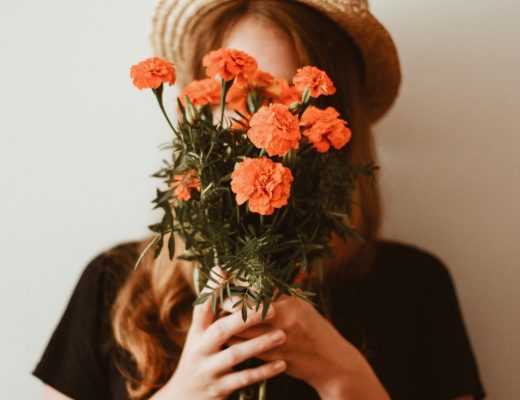 Woman wearing straw hat nad black tee holding orange flower bouquet in front of her face