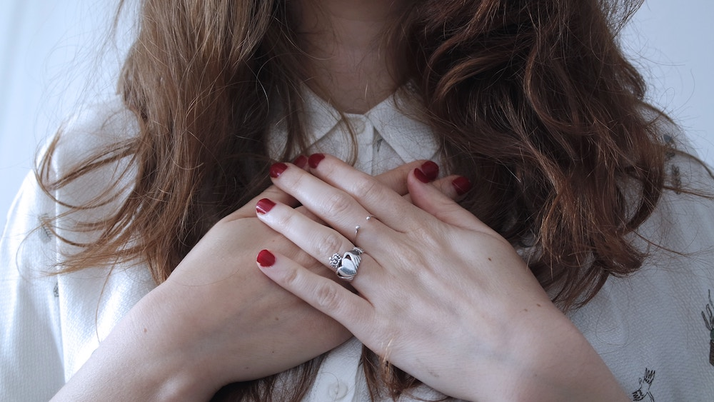 Ego or Intuition? How to Tell the Difference | Happy As Annie (Woman with red nail polish and clauddagh ring with hands crossed over her chest)