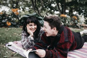 Two women laughing together with book laying on blanket in park