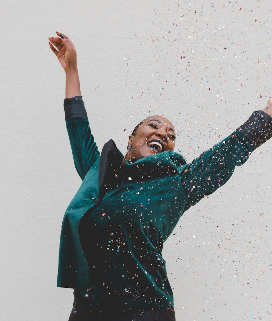 "Moving Toward Your True Destiny? How to Tell | Happy As Annie. Martha Beck's ""Shackles"" test from Steering by Starlight (Black woman wearing teal suit with hands raised joyfully in air as confetti falls around her)"