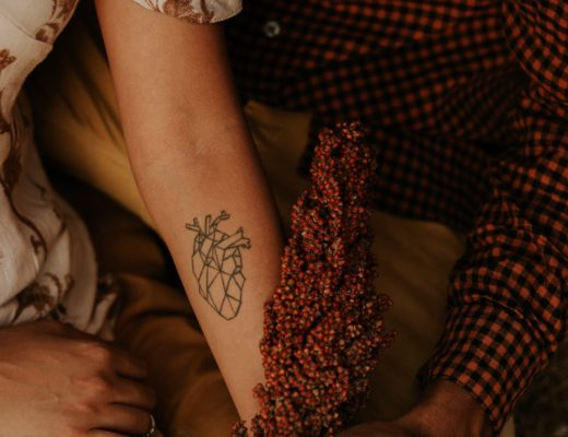 Woman in white and brown floral dress with heart organ tattoo on forearm holding hand of man in buffalo plaid shirt