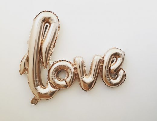 """gold """"love"""" word balloon against white background"""