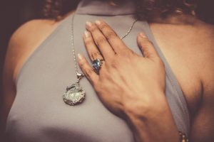 Woman with hand placed on chest, crystal ring and necklace