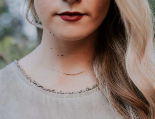 Woman with long blonde hair, red lips, and delicate necklace