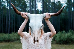 Girl in lace white dress holding up bull skeleton with horns in front of her face in woods