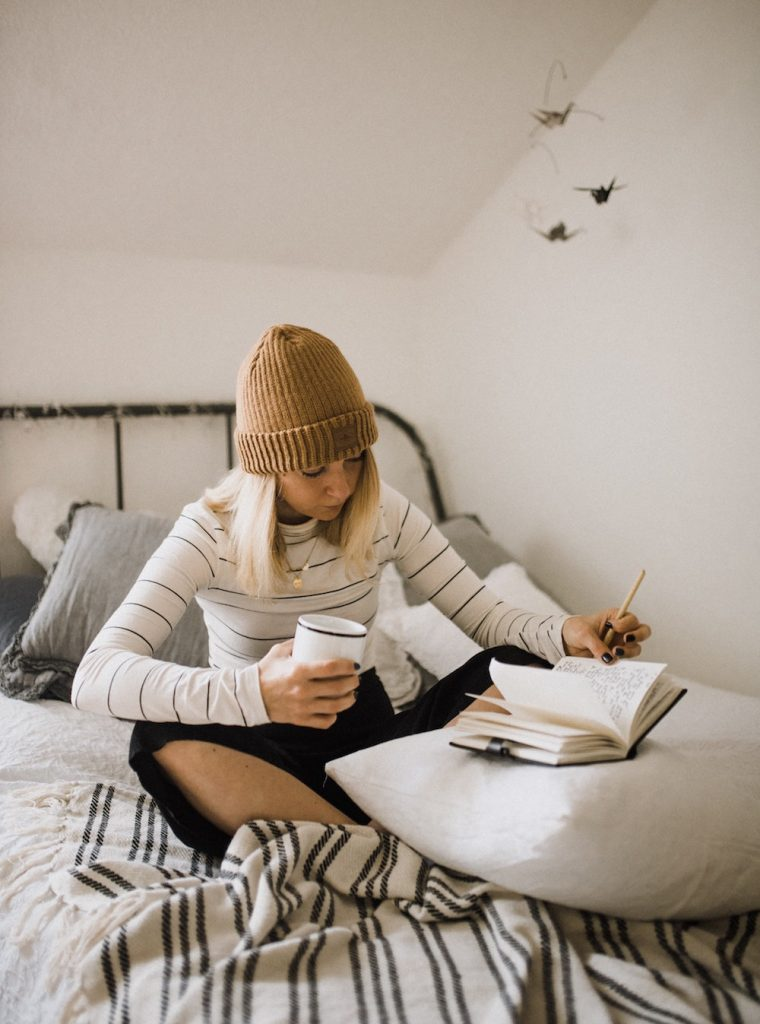 How to Interpret Your Dreams in 3 Steps | Happy As Annie | Best Life Book Club May selection is Steering by Starlight by Martha Beck, in which she explains how our intuition communicates with us through dreams. (Blonde woman in beanie holding coffee and jouranling in bed)
