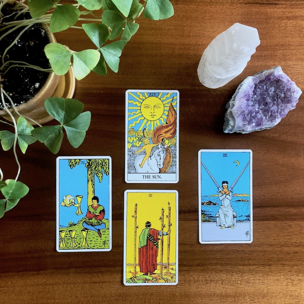 How to Shuffle Tarot Cards - Three Ways to Try Today | Happy As Annie - The classic Rider-Waite tarot deck is a great deck for beginners. (Four cards from Rider Waite deck on wooden table with potted plant and crystals)