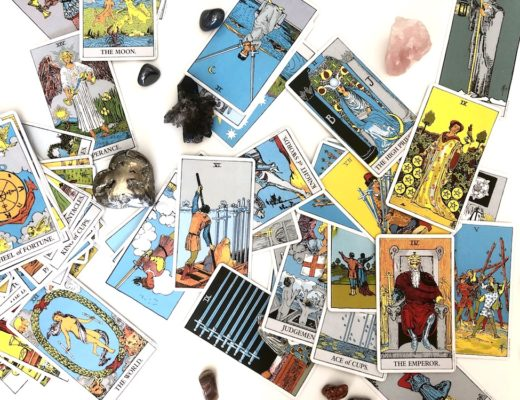 Jumble of Rider Waite tarot cards and crystals against white background