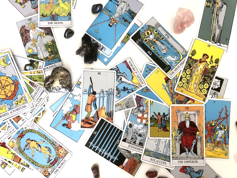 Happy As Annie | How to Bond with a New Tarot Deck - Bond with a new deck of tarot cards. Breaking in tarot cards. Connecting with your tarot cards. (Jumbled Rider-Waite tarot cards and diverse crystals laying on white table)