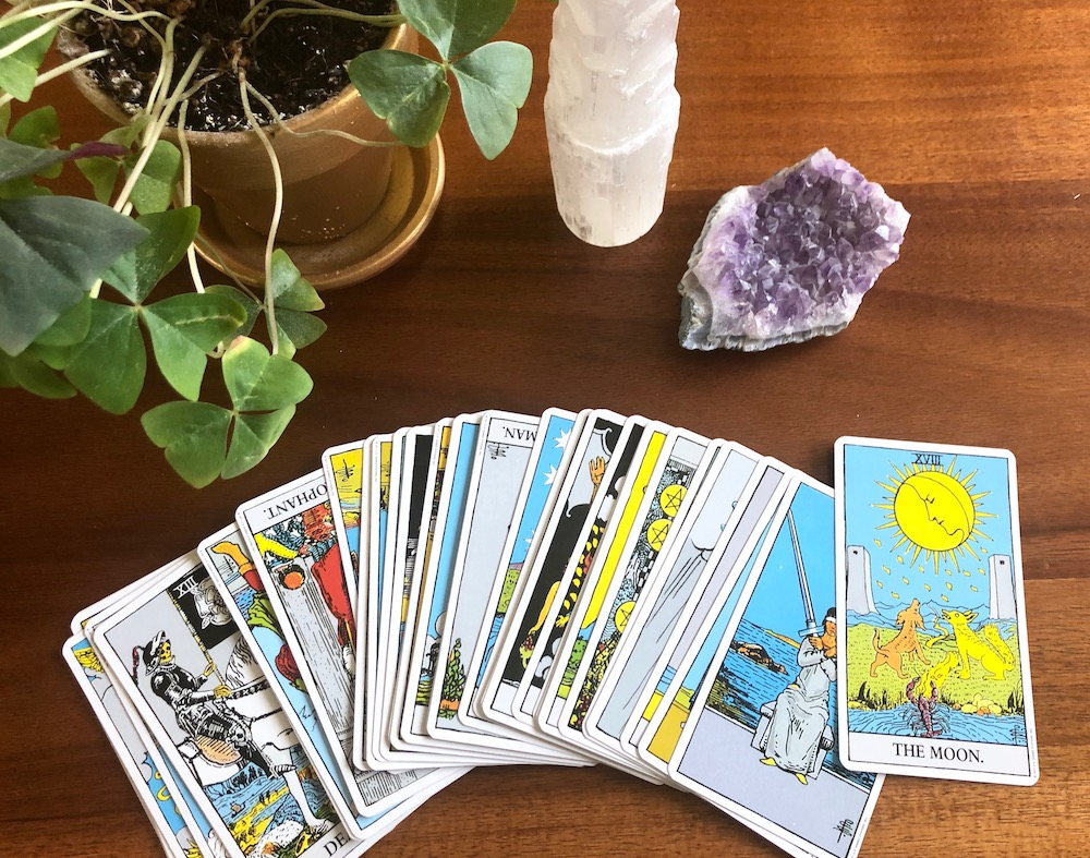 How to Break In and Cleanse Tarot Cards | Happy As Annie (The Moon and rest of Rider Waite tarot deck fanned across wooden table along with potted plant and crystals)