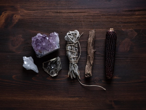 How to Break In and Cleanse Tarot Cards | Happy As Annie - How to Cleanse Tarot Cards with Crystals | There are so many ways to cleanse tarot decks. You can cleanse or bless a new tarot card with selenite or smoky quartz. (sage bundle, crystals, and other magical objects on wooden table)