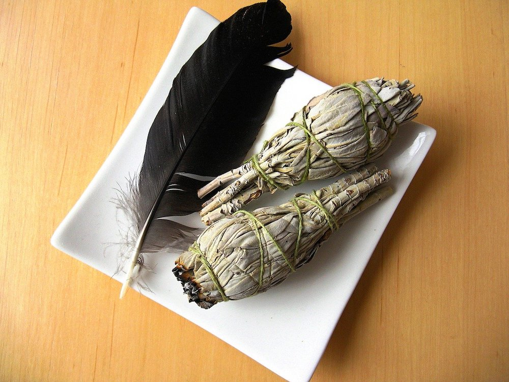 How to Cleanse a Space with Sage | Happy As Annie. How and why to burn sage to cleanse a space of negative energies. Practical tips and a step-by-step guide. #sage #burnsage #sagesmudge #sagewand (two sage bundles and black feather in white square dish on wooden table)