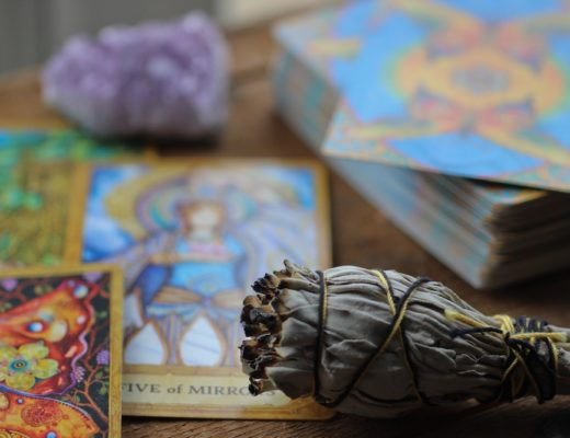 Tarot cards, amethyst, and sage bundle on wooden table
