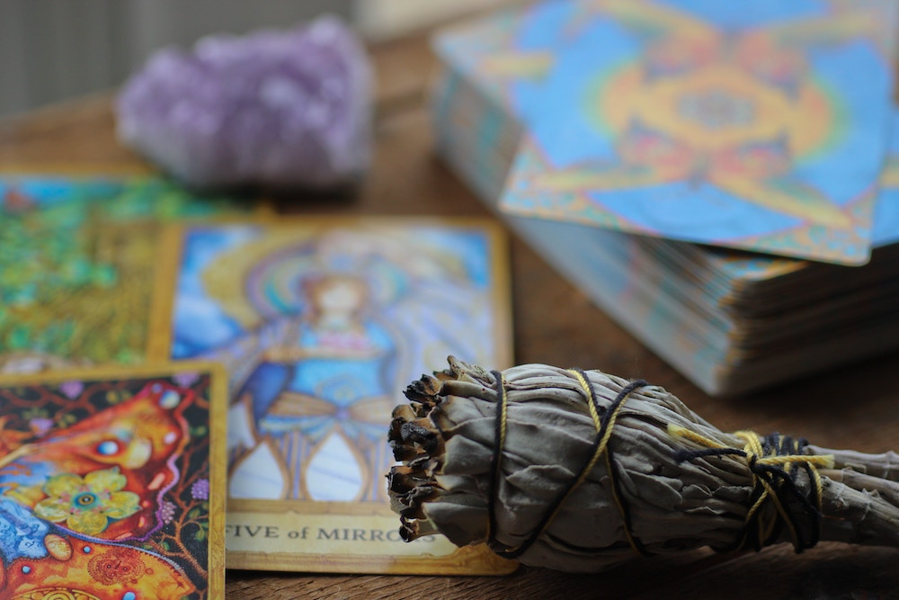 How to Break In and Cleanse Tarot Cards | Happy As Annie - How to cleanse tarot cards with sage or incense. Cleanse a tarot deck with sage or incense to cleanse the cards of negative energy. If you don't like to use sage, you can cleanse tarot cards without sage easily: use incense, crystals, a bell or sound bath, full moon light, or just shuffle. (Sage bundle, tarot cards, and amethyst on wooden table)