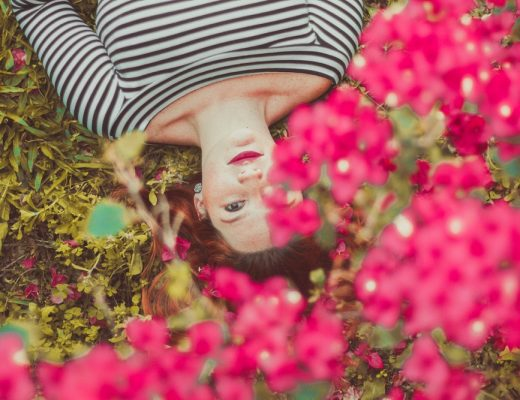 Woman wearing black and white striped boatneck tee laying down in grass with pink flowers in foreground