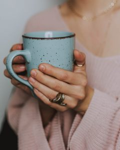 Girl in pink sweater holding blue mug with both hands, leaf ring