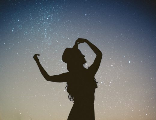 Woman's silhouette with arms up and wearing hat against starry sky background