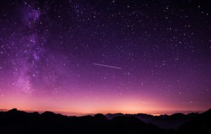 Shooting star across dark purple starry sky with mountains below