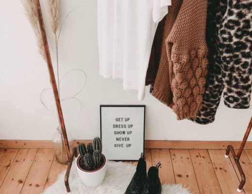Clothing rack with capsule wardrobe hanging and combat boots and framed quote on floor