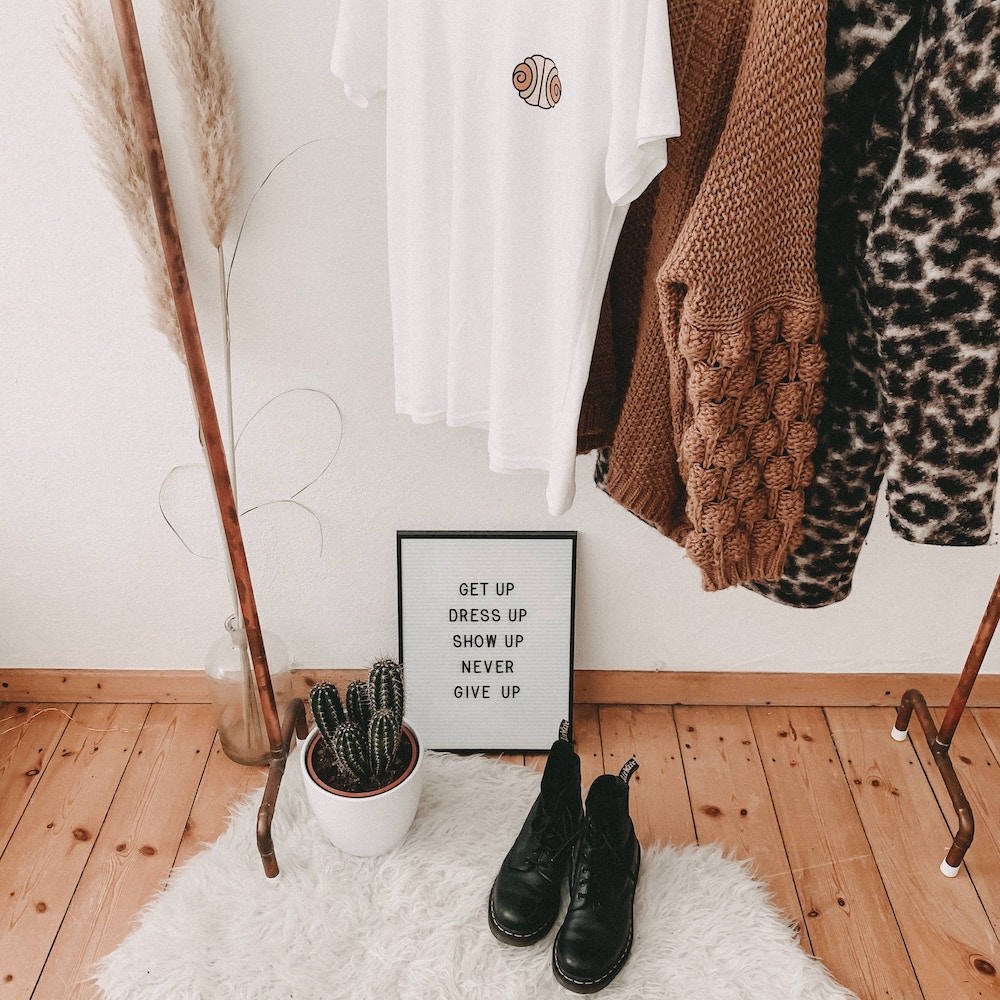 "How to Discover Your Authentic Style | Happy As Annie (clothing rack with sweaters and t-shirt hanging above a pair of boots, potted cactus plant, and framed text art that says ""GET UP DRESS UP SHOW UP NEVER GIVE UP"")"