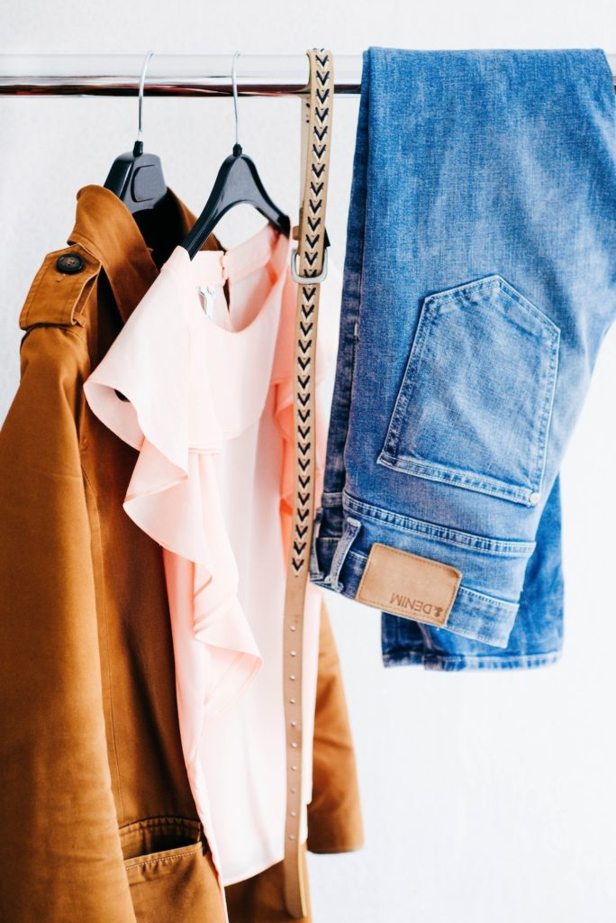 Metal clothing rack with brown jacket and pink top on hangers next to blue jeans and belt draped over bar