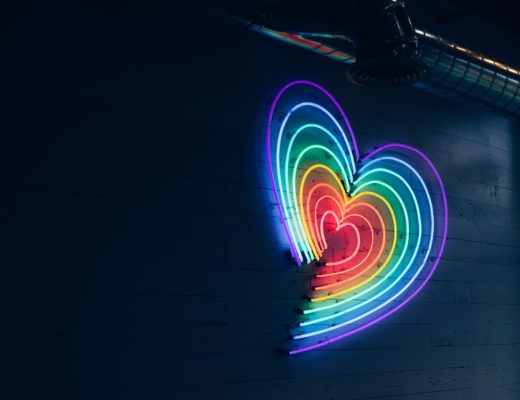 Neon light of rainbow colored concentric hearts