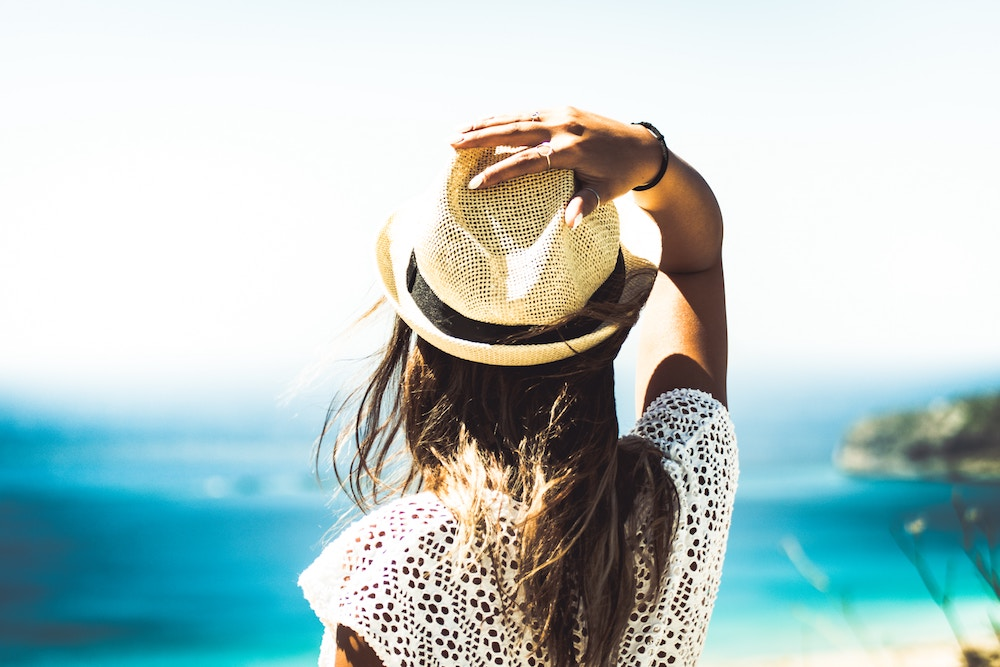 13 Essential Summer Must-Haves for Your Soul | Happy As Annie (Woman wearing straw hat looking out onto ocean)