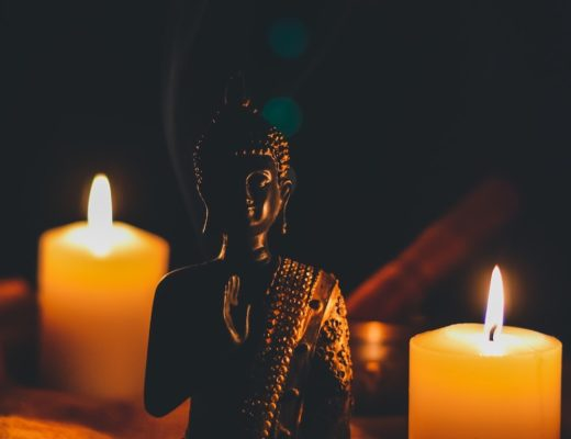 Small buddha figurine next to two lit votive candles