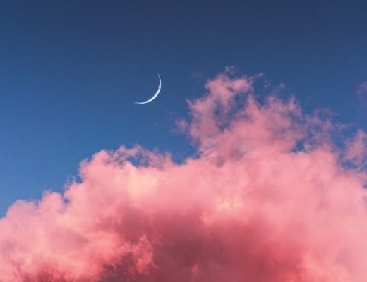 Thin crescent moon in blue sky with bright pink clouds