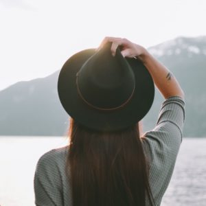 Woman wearing black hat looking off into distance with lake and mountain in background