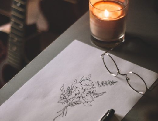 Candle in glass jar on table next to ink flower illustration and glasses
