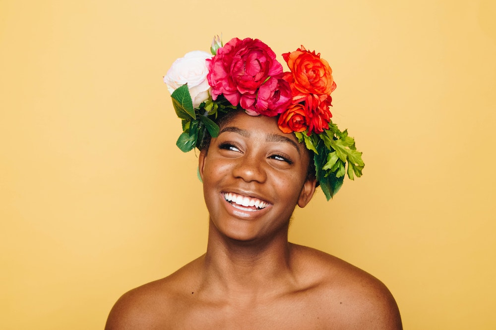 Woman with bare shoulders wearing colorful floral crown