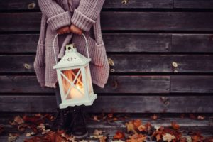 Girl wearing big purple cardigan and boots standing in fall leaves and holding white lantern