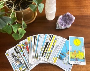 Rider Waite tarot cards fanned out with pictures facing up next to crystals and plant on wooden table