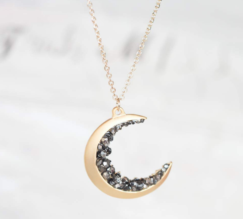 Gold plated crescent moon pendant encrusted with black crystals on The Ultimate Witchy Gift Guide by Happy As Annie