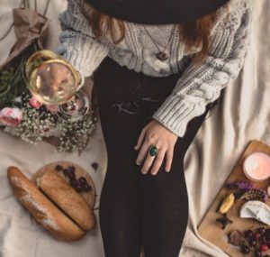 Modern witch sitting on white blanket with glass of wine in hand and food and flowers next to her